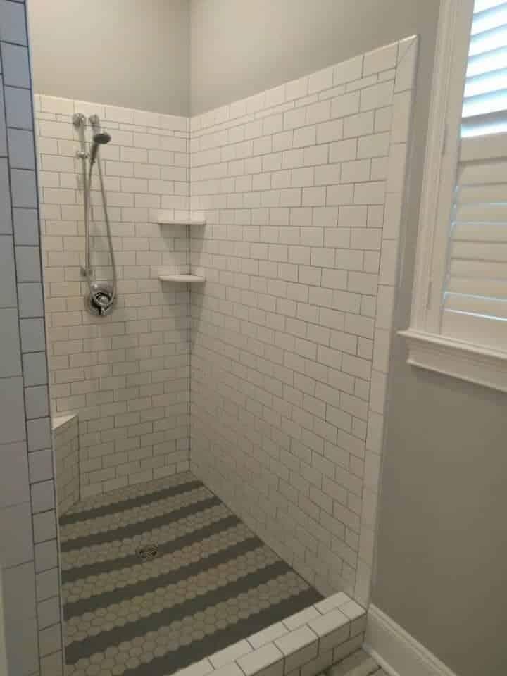 Ceramic tile shower walls with porcelain tile on floor